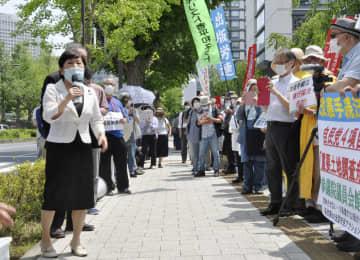 憲法改正手続きに関する改正国民投票法が成立し、国会周辺で抗議する市民と社民党の福島党首(左端)=11日午後