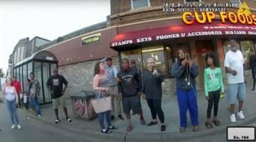 ジョージ・フロイドさんが逮捕される様子をスマートフォンで撮影するダルネラ・フレーザーさん(右から3人目)。警察官が装着したビデオカメラが捉えていた=2020年5月25日、米中西部ミネソタ州(ミネアポリ