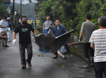 突風で飛ばされた倉庫の屋根や支柱を片付ける住民ら=21日午後7時10分、新富町新田