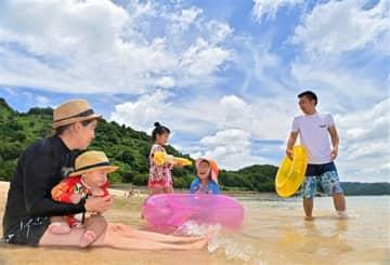 夏空の下、波打ち際で遊ぶ家族連れ=21日午後、芦北町の鶴ケ浜海水浴場