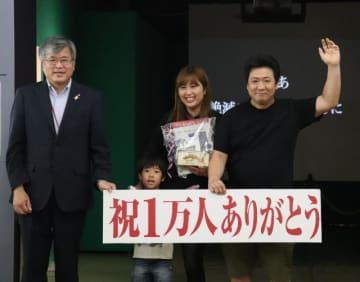 1万人目となった米倉佑馬さん(右)一家と県総合博物館の川口泰夫館長=21日午前、宮崎市・同館