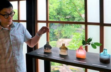 涼しげな色の一輪挿しなどガラス作品を展示する東さん(滋賀県東近江市五個荘川並町・ハクモクレン)