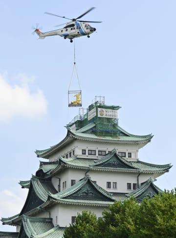 ヘリコプターで名古屋城の天守閣へ戻される「金のしゃちほこ」=22日午前、名古屋市