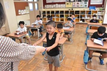 担任の先生から通知表を受け取る2年生=21日、深浦町の修道小