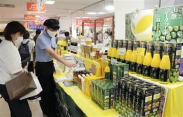 「おきなわフェア」でシークワーサージュースなどの特産品を品定めする来場客=21日、熊本市中央区