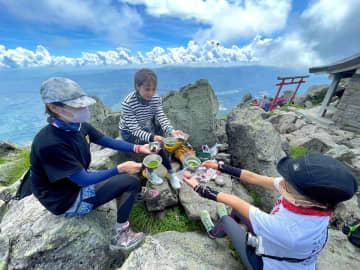 青空の下、涼しい風が吹く山頂で一服する登山客