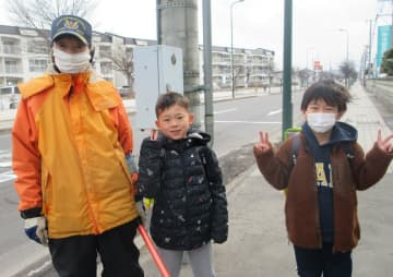 最後に街頭に立った3月25日、弘前市の西小学校の児童と写真に納まる中畑さん(左)(同小提供)