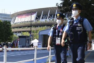 東京五輪の開会式が開かれる国立競技場と周辺を警備する警察官=22日午後
