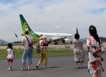 滑走路の近くで着陸する飛行機を見る参加者