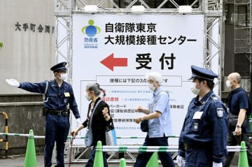 自衛隊が運営する新型コロナウイルスワクチン大規模接種センター東京会場に向かう人たち=5月、東京都千代田区
