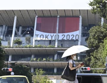 東京五輪の開会式が開かれる国立競技場近くを歩くマスク姿の人=22日午後