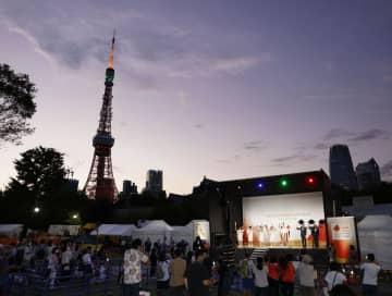 東京都港区の公園で行われた聖火の点火セレモニー。左は東京タワー=22日夕