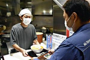 来場者に冷やしラーメンを提供する福地店主(左)