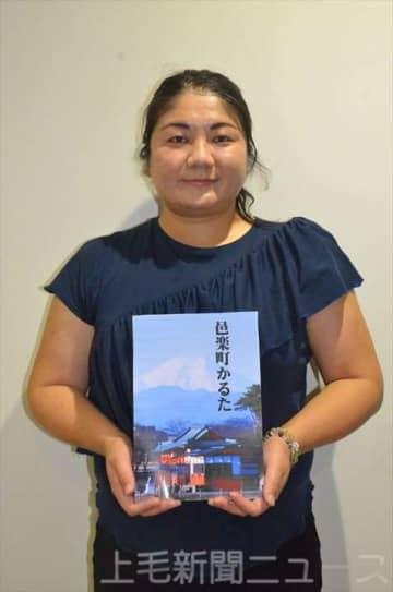 「邑楽町かるた」のパッケージに使う写真を持つ田村さん。多々良沼公園内の浮島弁財天と富士山が写る