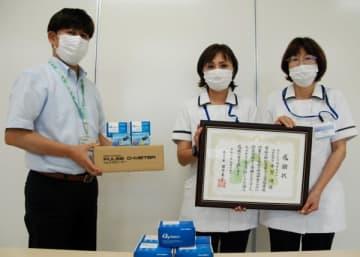 【パルスオキシメーターを持つ小林健康福祉部長(左端)と感謝状を持つ西村管理者(中央)ら=亀山市羽若町の市総合保健福祉センターで】