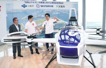 「空飛ぶクルマ」のモデル機を前に、福沢社長(右)から説明を受ける吉村知事(中央)と松井市長=14日、大阪市住之江区のATC