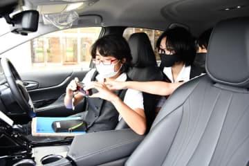 広告を制作する自動車の乗り心地などを確認する生徒たち=佐賀市の佐賀女子高