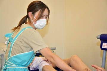 マスクをしながら入浴介助する八戸市の特養ホーム「瑞光園」の職員。人手不足から一時期、入浴介助を清拭に切り替えたこともあった(提供写真)