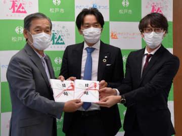 本郷谷市長(左)に抗原検査キットを寄贈した松本社長(中央)とロハス・メディカルの新岡辰徳代表取締役