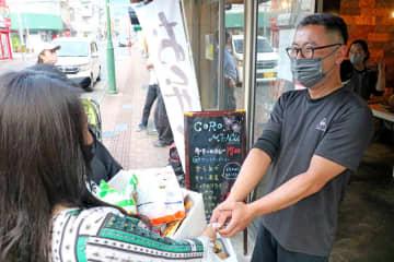 「こんなに頂いていいんですか?ありがとうございます」。柴田さん(右)から食料品を受け取った人々は口々にそう語った=佐世保市下京町