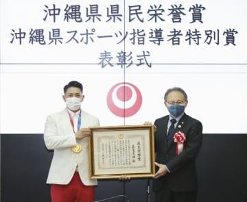 東京五輪の空手男子形で金メダルを獲得し、沖縄県の玉城デニー知事(右)から県民栄誉賞を授与された喜友名諒選手=15日午前、県庁(代表撮影)