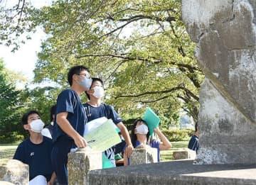 津波被害を伝える石碑に記された文字を確認する東朋中の生徒