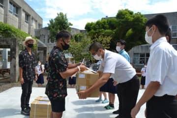 ベストアルバムとマスクを贈呈する A-RAさん(左端)と YOUさん(左から2人目)=15日、沖縄県宜野湾市・普天間中学校
