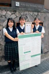 最優秀に選ばれたポスターを手にする(左から)小川千遥さん、脇阪紀恵さん、山本望実さん=神戸大付属中等教育学校
