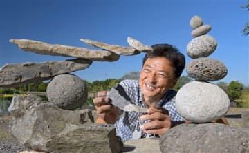 いろいろな形の石を使って、「ロックバランシング」の作品を作る佐藤清貴さん=9日、嘉島町の浮島神社