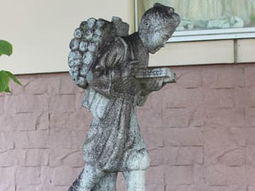 「帰郷」した二宮金次郎像を見つめる安藤浩孝さん=本巣郡北方町高屋分木、北方南小学校