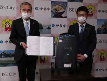 【協定書に調印した山田社長(左)と提供する医療用酸素濃縮装置=伊勢市役所で】