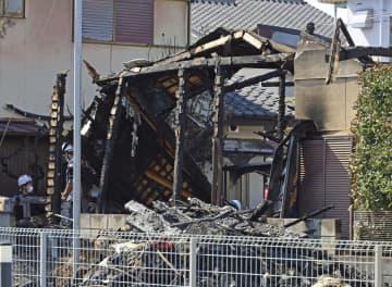 住宅が全焼した現場を調べる捜査員ら=14日午前、甲府市