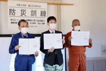 協定書に署名した(右から)田口会長、戸田社長、立会人の山野通彦町長