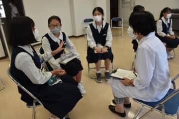 県総合農業試験場の職員(右)に仕事内容などについて質問する生徒ら