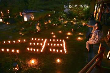 東林院で行われた夜間特別拝観「梵燈のあかりに親しむ会」の試験点灯=14日夕、京都市