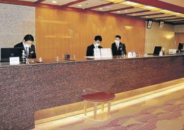 宿泊予約を受け付ける従業員。ワクチン接種者向けのプランが好調となっている=加賀市内の旅館