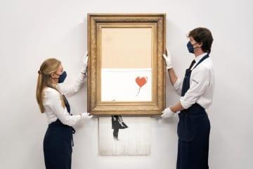 バンクシーの作品「愛はごみ箱の中に」を持つ展示担当者=9月3日、ロンドン(AP=共同)