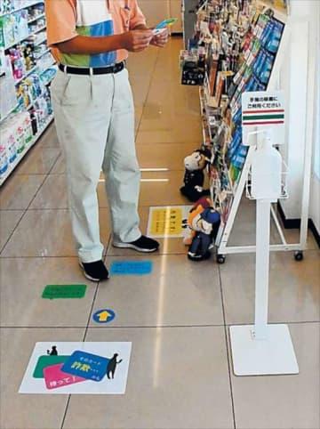 プリペイドカードの陳列棚まで誘導し、詐欺への注意を呼び掛けるシールが貼られた店内