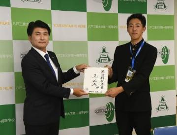 西武の水澤英樹スカウト(左)から辻発彦監督のサイン色紙を受け取る工大一の黒田将矢=14日、同校