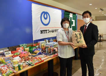 【社員が持ち寄った食料品を前に青木代表(左)にコメを手渡す藤井取締役=津市丸之内で】