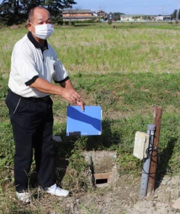 【田んぼダムのせき板と水位計を示す安達代表=松阪市清水町で】