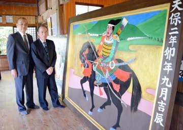 修復された大絵馬。武者の勇壮な姿を描いている。修復に当たった中村啓三さん(左)と杉光定さん=鹿島市の五の宮神社