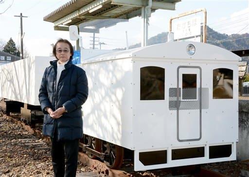 「新車両(写真後方)を観光振興につなげたい」と話す高千穂あまてらす鉄道の高山文彦社長=宮崎県高千穂町