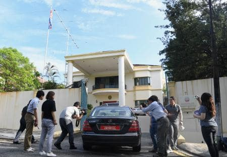 クアラルンプールの北朝鮮大使館に入る車と報道陣=25日(共同)