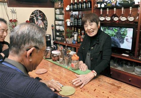 カウンター越しに常連客と笑顔で言葉を交わす日置美奈子さん=熊本市中央区下通