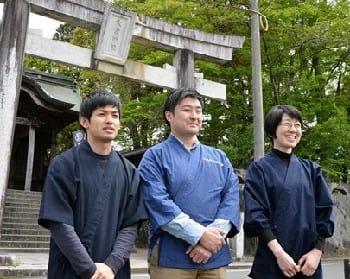神事の後、大宮神社の前に立つ新顔の灯籠師たち。左から中村潤弥さん、中島弘敬さん、坂本ゆかりさん=21日、山鹿市