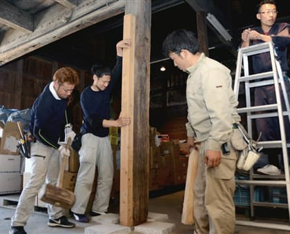 倉庫の柱のゆがみを矯正する九州大工志の会のメンバーら=27日、熊本市南区