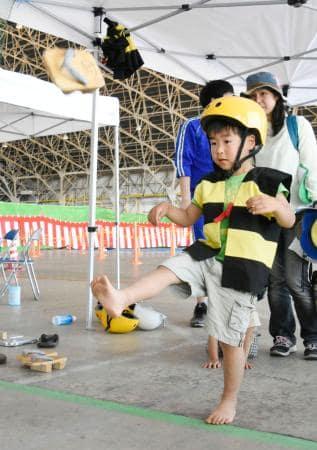 「第19回ゲゲゲの鬼太郎ゲタ飛ばし大会」で、げたを蹴り上げる子ども=28日午後、鳥取県境港市の航空自衛隊美保基地