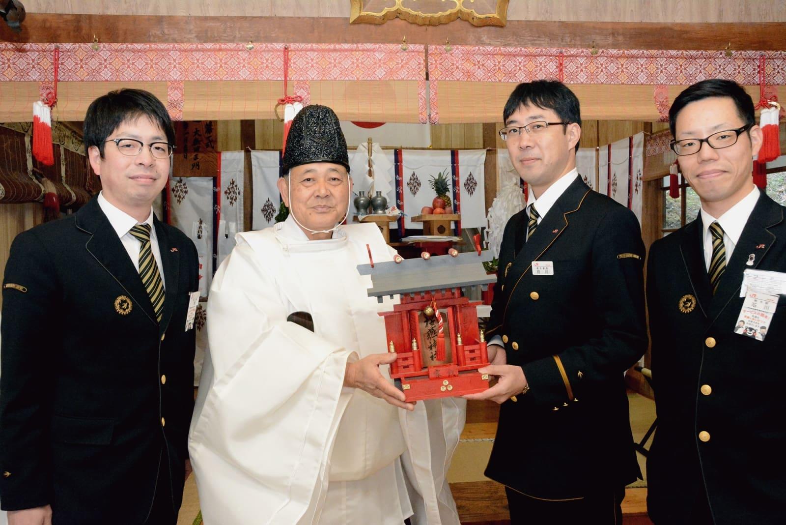 尾方嘉春宮司(左から2人目)から神殿を受け取る持月裕如駅長(同3人目)