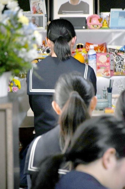 男子生徒の遺影の前で手を合わせる同級生=14日、福井県池田町
